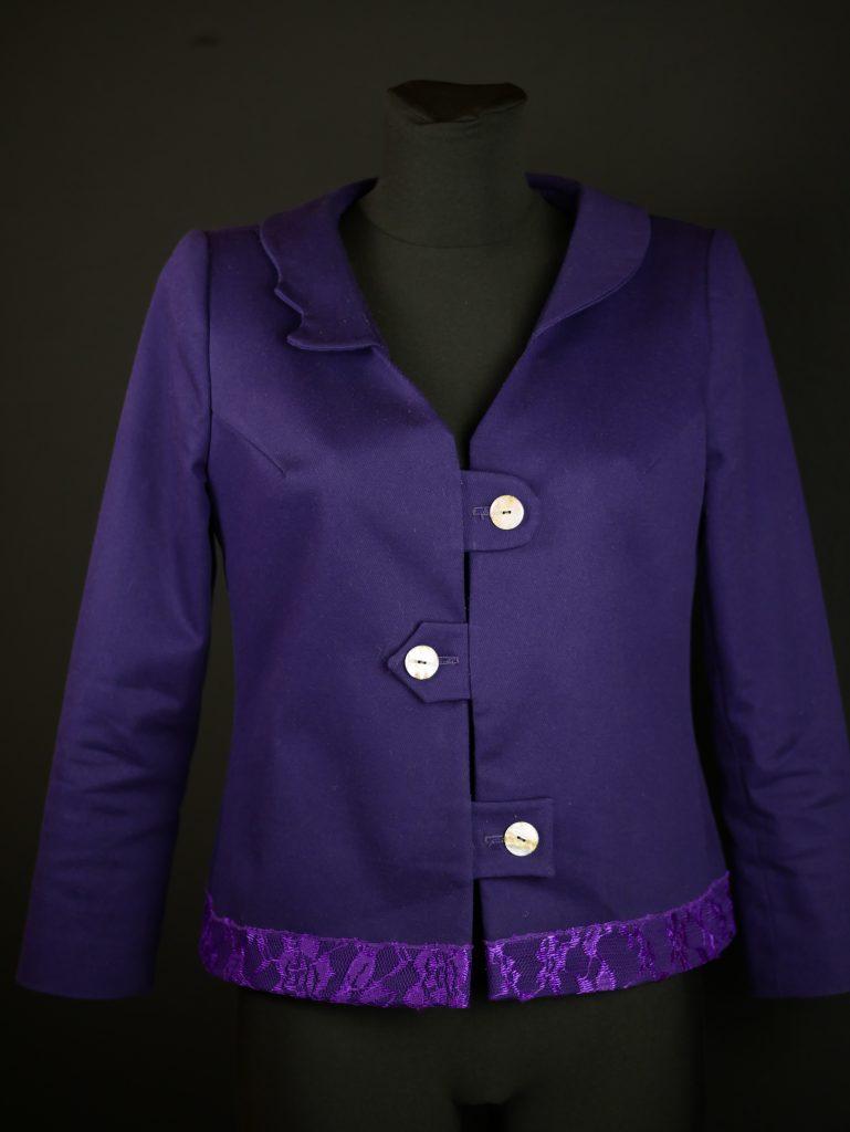 Jacke, leichte, gerade Form, asymetrische Verschlusslösung mit Knöpfen. Ein asymetrischer Kragen wirkt überraschend und etwas Spitze schmückt den Saum