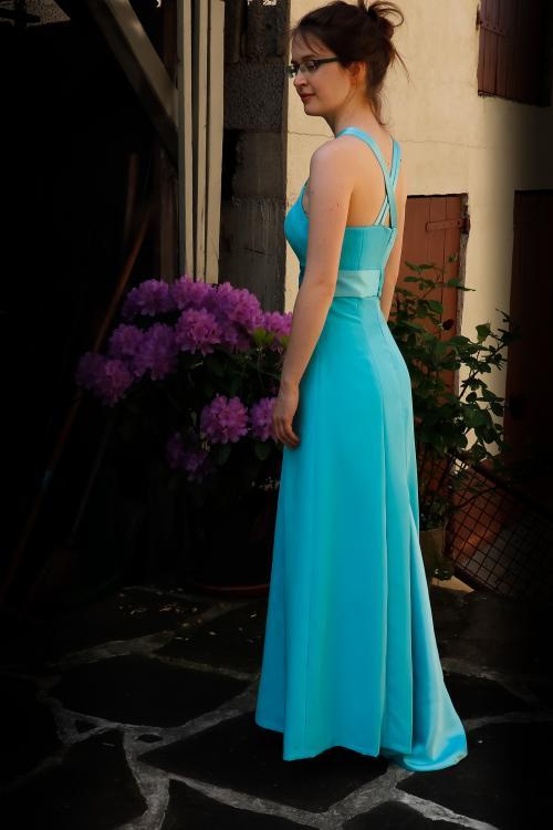 seitliches Bild des Kleides: edle Paspelierung, glänzende Träger und Schleppe, Schnittführung, die die zarten Proportionen betont